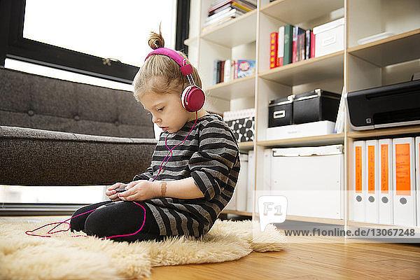 Mädchen  das zu Hause über Kopfhörer Musik hört