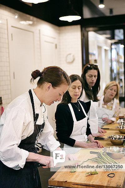 Schülerinnen und Schüler sehen im Kochkurs den Koch beim Zerkleinern von Gemüse