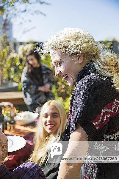Seitenansicht einer glücklichen Frau im Gespräch mit Freunden auf einer Gartenparty