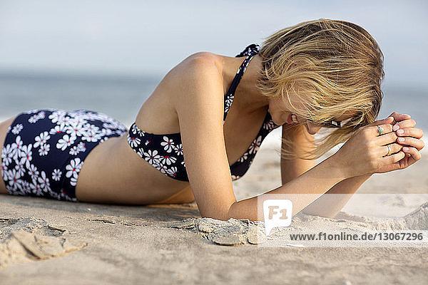 Seitenansicht einer Frau  die sich am Strand im Sand entspannt