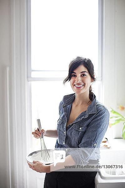 Porträt einer Frau  die zu Hause Schlagsahne zubereitet