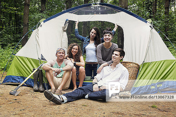 Friends by tent in forest