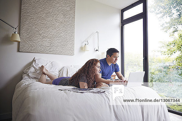Couple looking at laptop computer while resting on bed by window