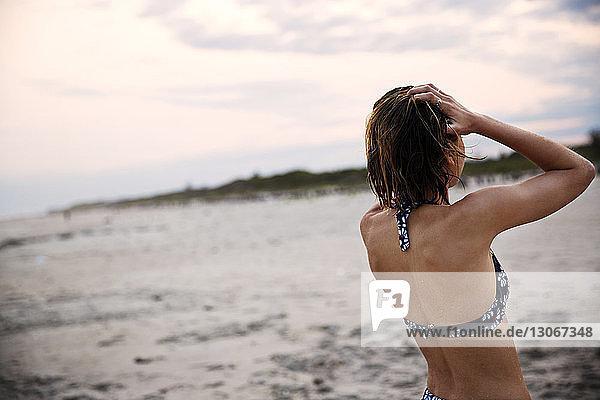 Rückansicht einer Frau mit Händen in Haaren  die gegen den Himmel stehen