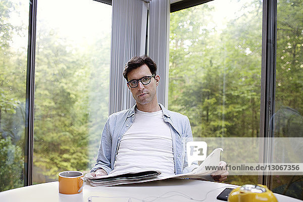 Portrait of man holding newspaper while having tea at table against window