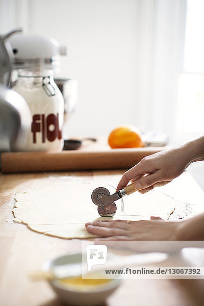 Cropped image of woman cutting pastry dough through cutter for preparing pie