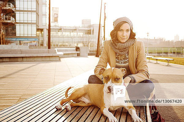 Portrait of woman with dog sitting on bench