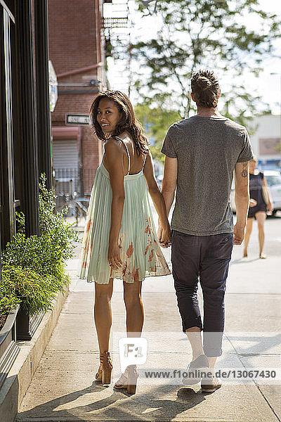 Rückansicht eines Paares  das an einem sonnigen Tag auf dem Bürgersteig geht