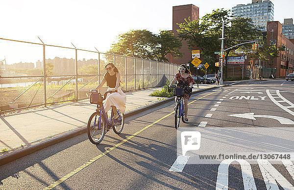 Glückliche Freundinnen fahren Fahrrad auf der Straße in der Stadt