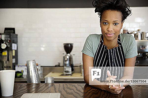 Porträt eines selbstbewussten Besitzers  der am Tresen im Cafe steht