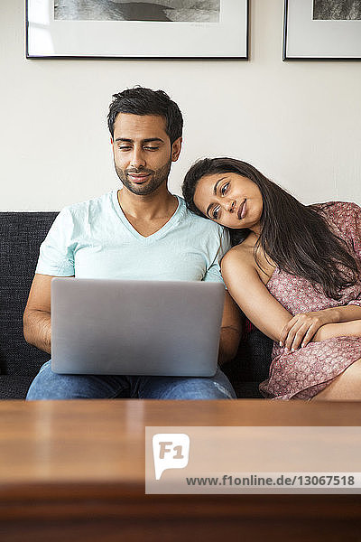 Couple using laptop computer while sitting on sofa at home