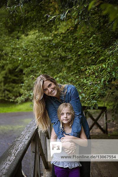 Porträt einer lächelnden Mutter und Tochter  die am Geländer vor Pflanzen im Hof stehen