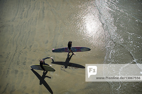 High angle view of friends with surfboards walking on shore at beach