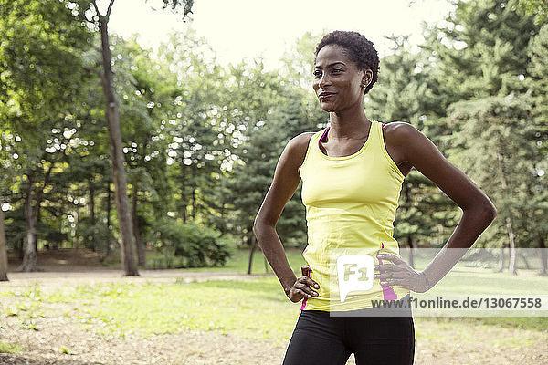 Lächelnde Frau mit Händen auf der Hüfte  die weg schaut  während sie im Park auf dem Feld steht