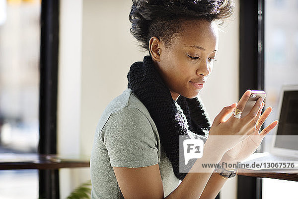 Woman using mobile phone while sitting in cafe