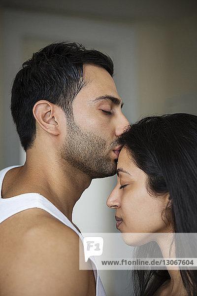 Seitenansicht eines Mannes  der eine Frau auf die Stirn küsst