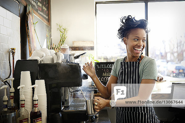 Happy woman looking away while making coffee in cafe