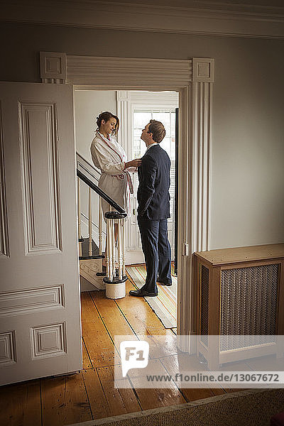 Woman holding man's tie while standing on staircase at home