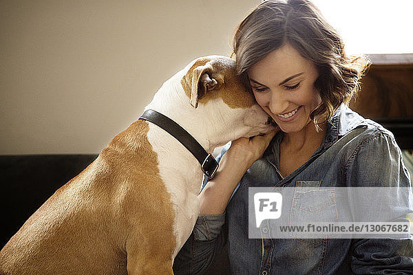 Happy woman playing with dog at home