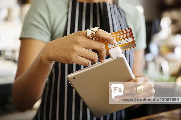 Mittelsektion einer Frau  die ein Kreditkartenlesegerät in einem Cafe benutzt