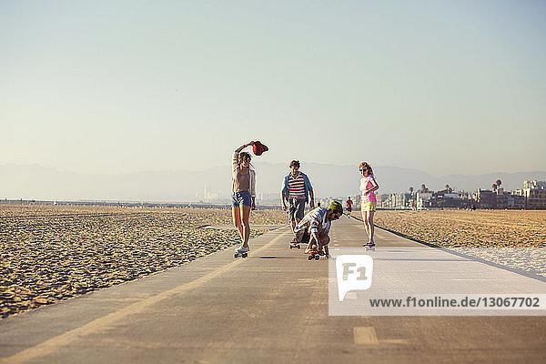 Freunde skateboarden auf der Straße gegen den klaren Himmel