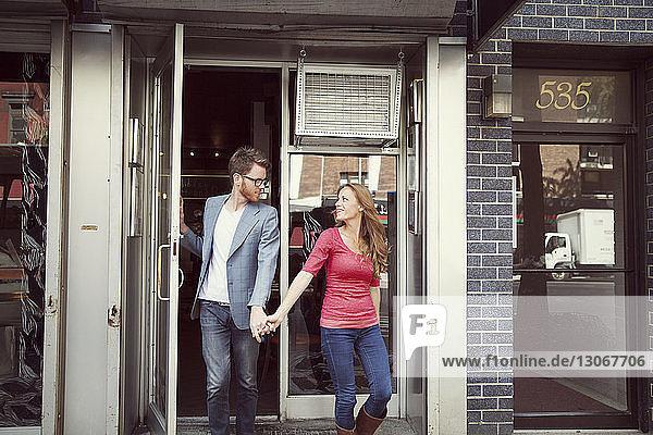 Paar  das beim Verlassen des Restaurants Händchen hält