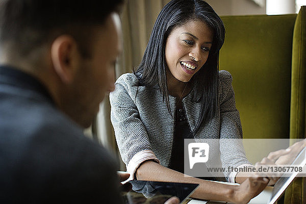Woman showing tablet computer to colleague in office