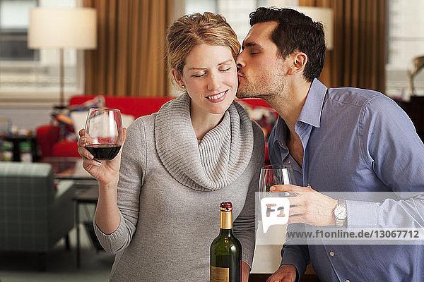 Mann küsst Freundin mit Weinglas