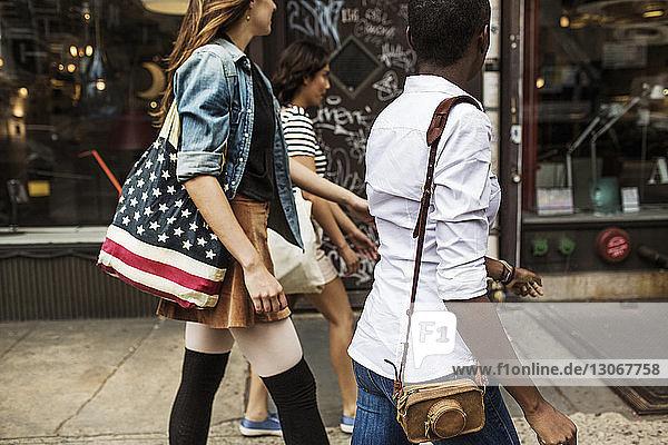 Freunde spazieren auf einem Fußweg in der Stadt