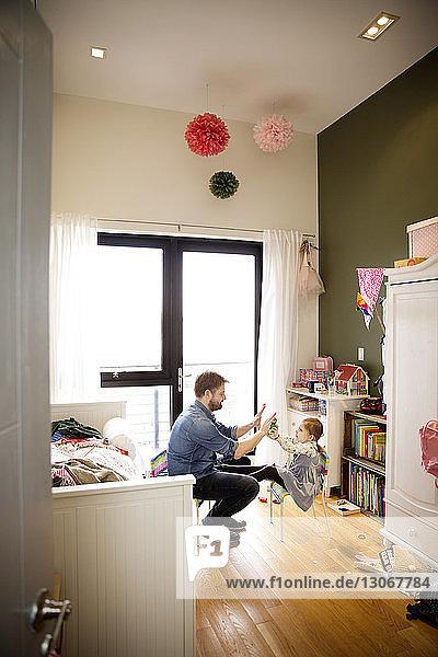 Seitenansicht von Vater und Tochter beim Spielen  während sie zu Hause auf einem Stuhl sitzen
