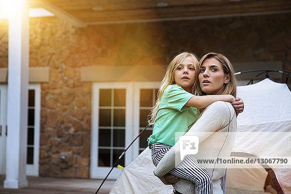 Nachdenkliche Mutter und Tochter stehen mit Zelt gegen Haus