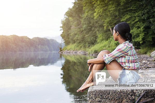 Seitenansicht einer Frau  die auf einem Felsen gegen einen See im Wald sitzt