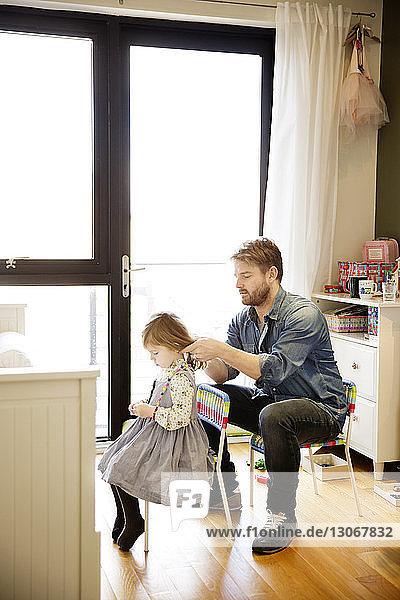 Vater bindet der Tochter zu Hause die Haare