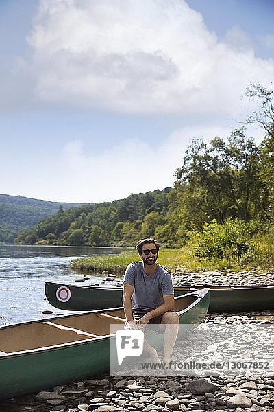 Lächelnder Mann sitzt im Kanu am Seeufer gegen den Himmel