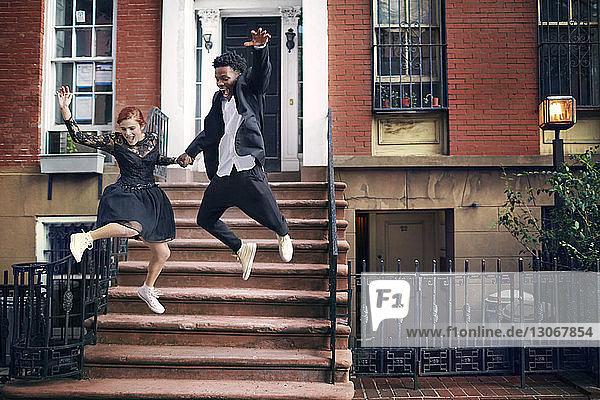 Fröhliches Paar springt gegen Haus
