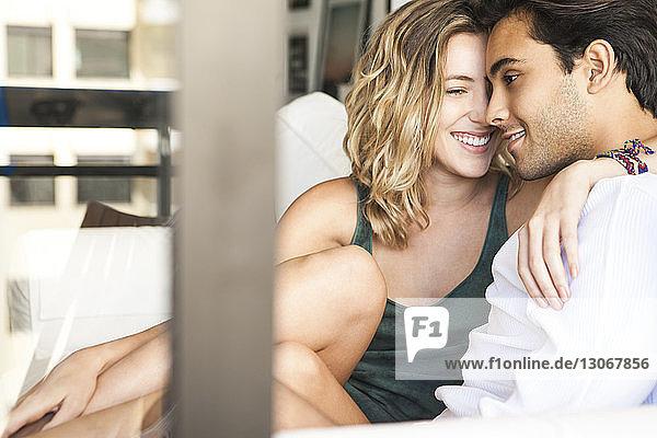 Fröhliches Paar sitzt auf dem Sofa