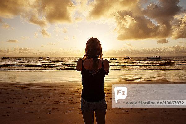 Rückansicht einer Frau  die bei Sonnenuntergang am Strand steht