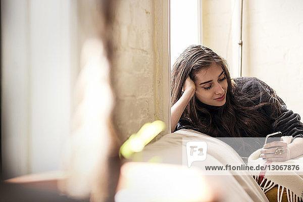 Frau mit Hand im Haar  die ein Smartphone benutzt  während sie sich zu Hause auf das Sofa lehnt