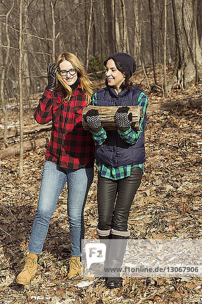 Woman carrying firewood while walking with friend in forest