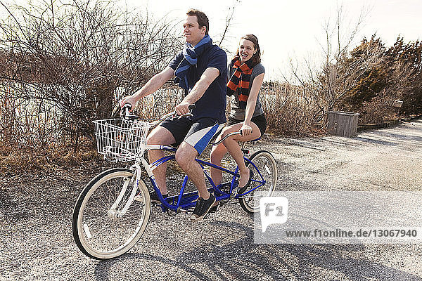 Happy couple riding tandem bicycle against clear sky