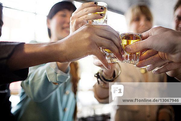 Freunde stoßen in einer Bar auf Tequila-Shots an