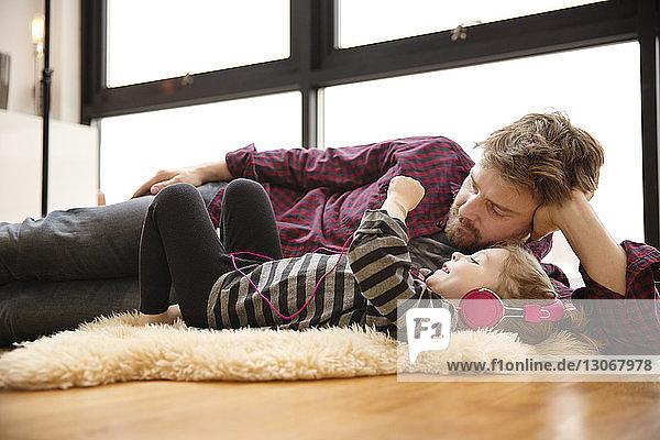 Mädchen hört Musik vom Vater  während sie zu Hause auf dem Boden liegt