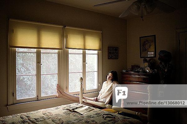 Frau sitzt zu Hause am Fenster