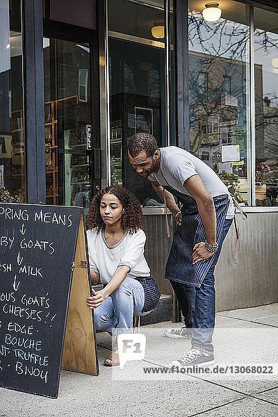 Frau schreibt an die Tafel  während der Mann vor den Laden schaut
