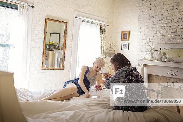 Freunde spielen Kartenspiel  während sie zu Hause im Bett sitzen