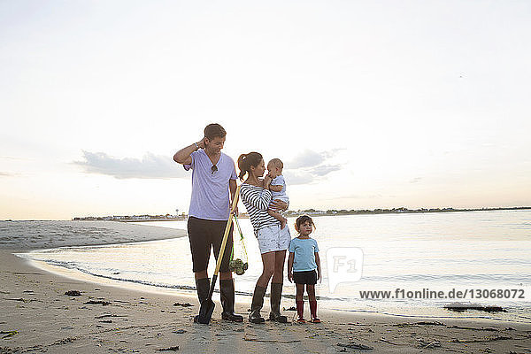 Full length of family standing on beach against sky
