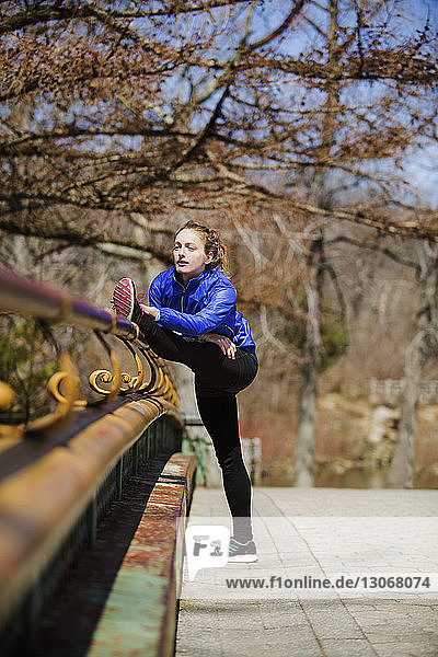Woman practicing stretching exercise by railing at park