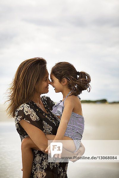 Mother and daughter rubbing noses while standing at beach