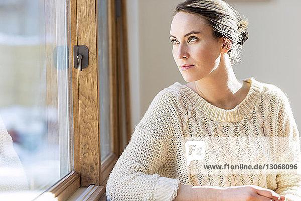 Frau schaut weg  während sie zu Hause am Fenster sitzt