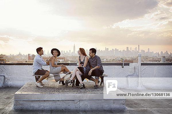 Glückliche Freunde unterhalten sich  während sie sich bei Sonnenuntergang auf der Terrasse des Gebäudes ausruhen